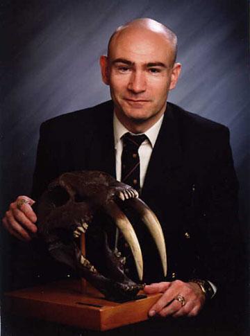 Shuker with the skull of the extinct smilodon. Photo courtesy of Karl Shuker.