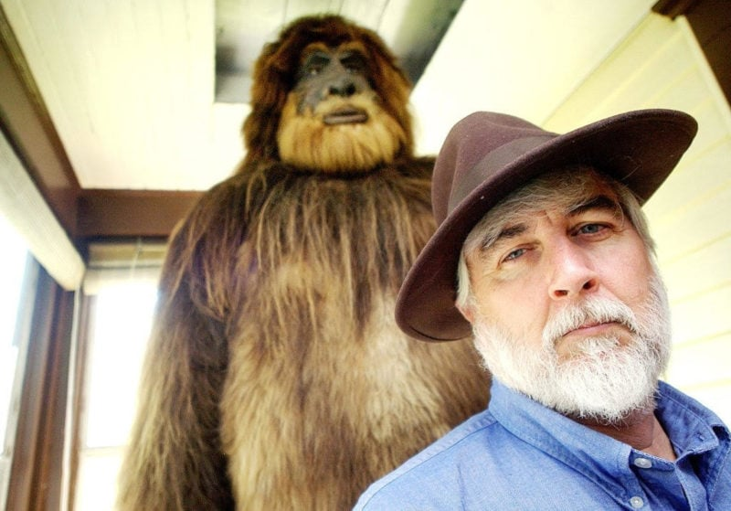 man in hat in front of bigfoot statue