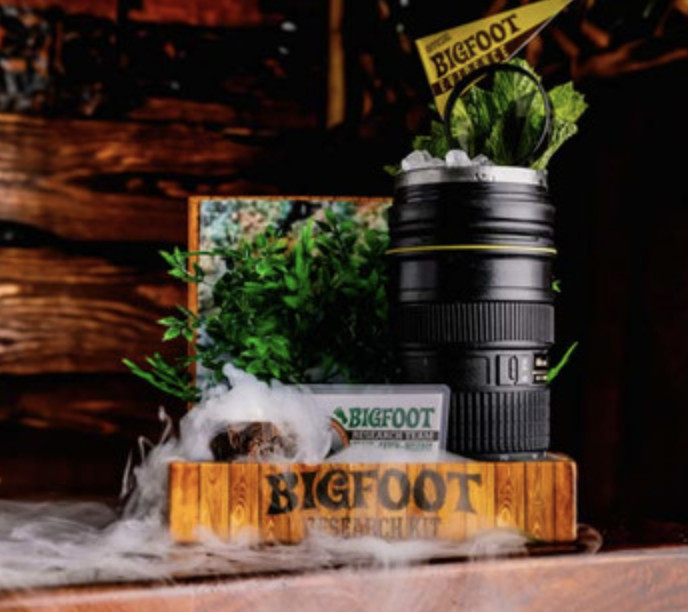 """A cocktail mug in the shape of a black camping canteen, with dry ice flowing over a small wood sign that says """"Bigfoot"""""""